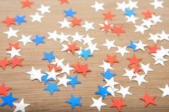 Konfettistjärnor på träbakgrund 4th Juli, självständighetsdagen, kortet, inbjudan i USA sjunker färger Sikten från överkant, tömm Arkivfoto