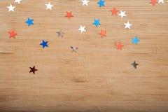 Konfettistjärnor på träbakgrund 4th Juli, självständighetsdagen, kortet, inbjudan i USA sjunker färger Sikten från överkant, tömm Royaltyfri Fotografi