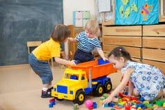 Konflikt för två ungar för leksaklastbil i dagis royaltyfri foto