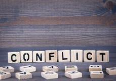 Konfliktwort geschrieben auf hölzernen Block Dunkler hölzerner Hintergrund mit Beschaffenheit Stockbild