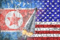 Konfrontation mellan USA och Nordkorea Hot av det kärn- slaget Flaggorna av två länder målade på betongväggen Royaltyfri Bild