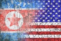 Konfrontation mellan USA och Nordkorea Hot av det kärn- slaget Flaggorna av två länder målade på betongväggen Arkivfoton