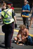 konfrontera den shirtless polisen för kvinnligmantjänsteman Arkivfoto