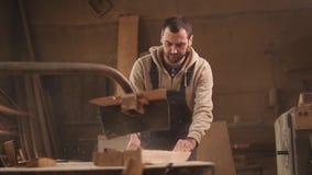 Konfrontieren Sie, schließen Sie herauf Gesamtlänge des Sawingholzes auf einer Kreismaschine Tischler im Overall stock footage
