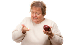 Konfuse ältere Frauen-Holding Apple und Vitamine Stockfotografie