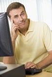 Konfuser Mann auf einem Computer Stockbilder
