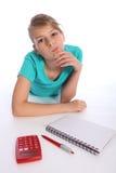 Konfuses Schulemädchen, das an Matheheimarbeit denkt Stockfotografie