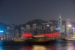 Kong Kong Financial District with a boat passing in front Royalty Free Stock Photo