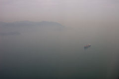 Kong Kong mist and ship. Aerial photo of a ship waiting to enter Hong Kong harbour Royalty Free Stock Images