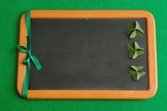 Koniczyny i zielony faborek wystawiający na czarnej desce Fotografia Royalty Free