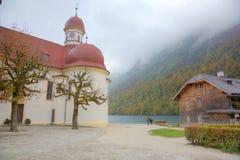 湖Konigssee美好的风景有著名Sankt Bartholomae朝圣教会的由湖边和秋天山在有雾 库存照片