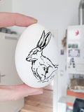 Konijn die op wit ei voor Pasen trekken Royalty-vrije Stock Fotografie