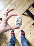 Konijn die op wit ei voor Pasen trekken Royalty-vrije Stock Foto's