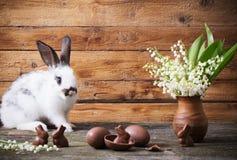 Konijn met chocoladeeieren en bloemen Stock Foto's