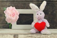 Konijnpop die rode hartvorm houden dichtbij leeg kader royalty-vrije stock afbeeldingen