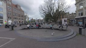 Koningsplein with people on benches and tram passing by. Amsterdam, Netherlands. Amsterdam, Netherlands - August 09, 2016: Koningsplein with people relaxing on stock video