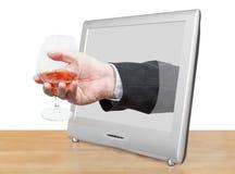 Konjakexponeringsglas i den manliga handen lutar ut TVskärmen Arkivfoto