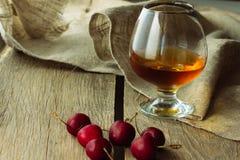 Konjakexponeringsglas och svart körsbär Arkivfoto