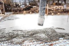 Konkret automatiskt pumprör som arbetar på fundament av konstruktionsplatsen arkivfoton
