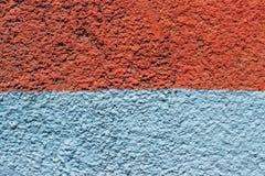 Konkret bakgrund som målas med apelsinen, och blått målar royaltyfri bild