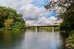 Konkret bro över rävfloden på en molnig dag arkivbild