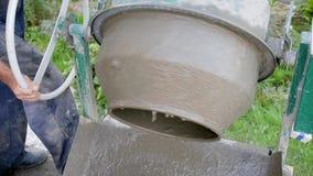 konkret hälla Blandande mortel för byggnadsarbetare Hällande konkret blandning från cementblandare Konstruktionsprocessen stock video