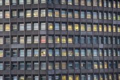 Konkret kontorsbyggnad med upplysta fönster Royaltyfri Foto