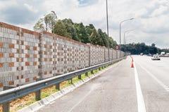Konkret oväsenbarriärvägg längs den upptagna bullriga huvudvägen Royaltyfri Fotografi