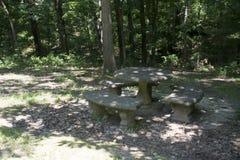 Konkret picknicktabell i en parkera Arkivfoto