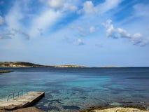 Konkret pir med ett turkosblåtthav i eftermiddagen med blå molnig himmel arkivbild