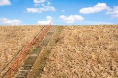 Konkret trappa upp en gräskulle Arkivfoto
