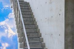 Konkret trappuppgång med himmel- och molnbakgrund arkivfoto