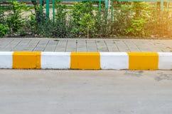 Konkret trottoar med guling- och vittrottoarkanten Arkivbilder
