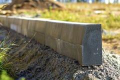 Konkret trottoarkantinstallation arbetar på vägkonstruktionsplatsen Grund DOF Royaltyfri Fotografi
