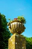 Konkreta blomkrukor i trädgården på en sockel stiliserade antiqu Arkivfoton