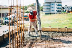 Konkreta hällande detaljer - industriell man som arbetar på huskonstruktionsplats arkivbilder