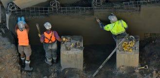 Konkreta murbrukmän som slätar betongväggen Royaltyfri Foto