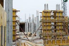 Konkreta pelare som stöttas med bräden på konstruktionsplats Arkivfoto