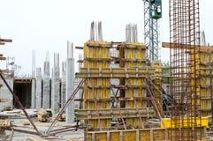 Konkreta pelare som stöttas med bräden på konstruktionsplats Arkivbild