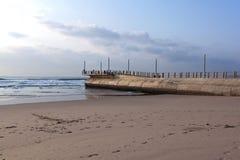 Konkreta Pier Protruding från havet på lågvatten royaltyfria foton