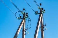 Konkreta poler med elektriska trådar och hög-spänning fördelningsisolatorer som delen av en överföringslinje royaltyfria foton