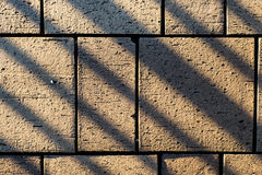 Konkreta stenläggningkvarterstenar med den vinkelformiga linjen skuggar Royaltyfria Foton