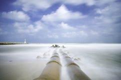 Konkrete Abflussrohrleitung an der Küstenlinie weich weiße Welle, die den Strand wegen der langen Belichtung schlägt Stockbilder