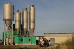 Konkrete Fabrik mit Warte-LKWs im Sonnenuntergang Stockfotografie