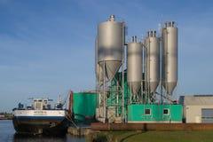 Konkrete Fabrik mit Warteschiff im Sonnenuntergang Lizenzfreies Stockfoto