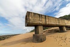 Konkrete Rohrleitung, die auf Strand und Rocky Coastal Seasc verlängert Stockfoto