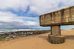 Konkrete Rohrleitung, die auf Strand und Rocky Coastal Seasc verlängert Stockfotos
