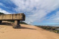 Konkrete Rohrleitung, die auf Strand und Rocky Coastal Seasc verlängert Lizenzfreies Stockbild
