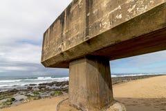 Konkrete Rohrleitung, die auf Strand und Rocky Coastal Seasc verlängert Stockfotografie