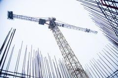 Konkrete Säulen auf Industriebaustandort Gebäude des Wolkenkratzers mit Kran, Werkzeugen und Bewehrungsstahlstangen lizenzfreie stockbilder